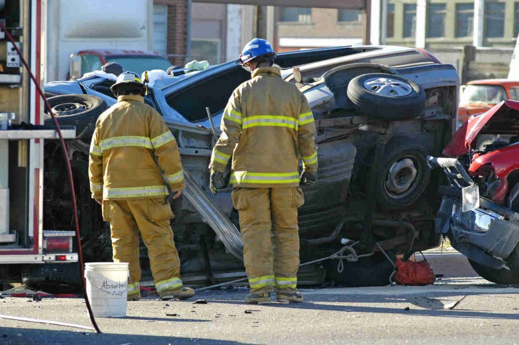 firefighters examine car accident scene