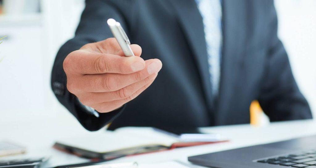 insurance adjuster offering pen to sign settlement offer
