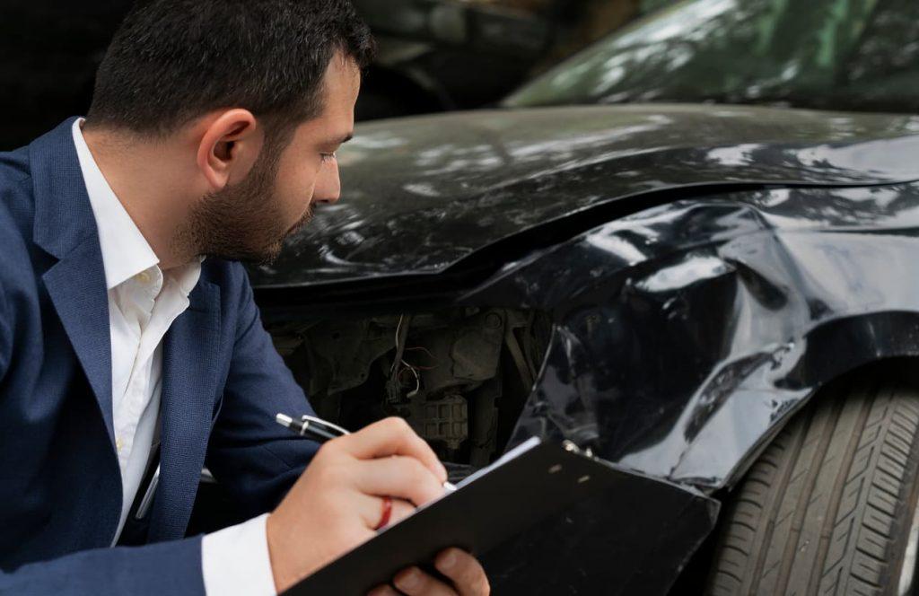 insurance adjuster examining car damage