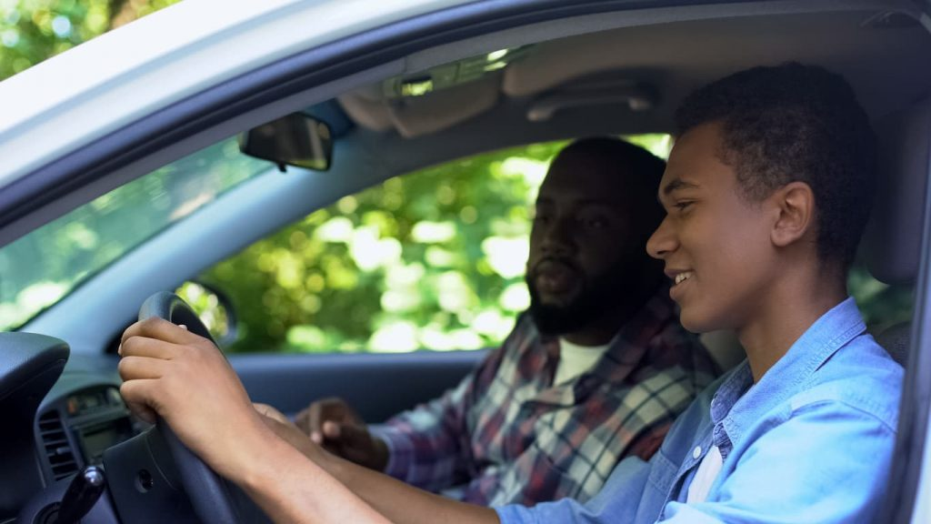 father teaching teenage son how to drive safely