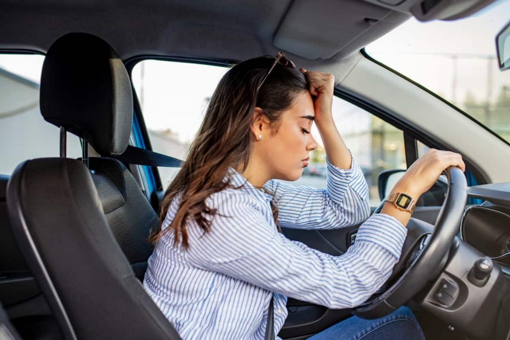 woman with anxiety behind the wheel of a car