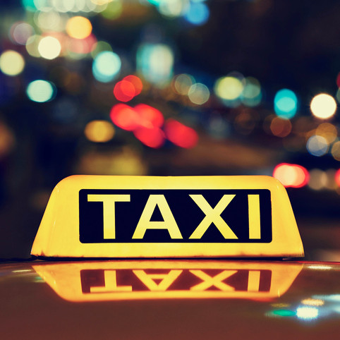 taxi sign on top of a car